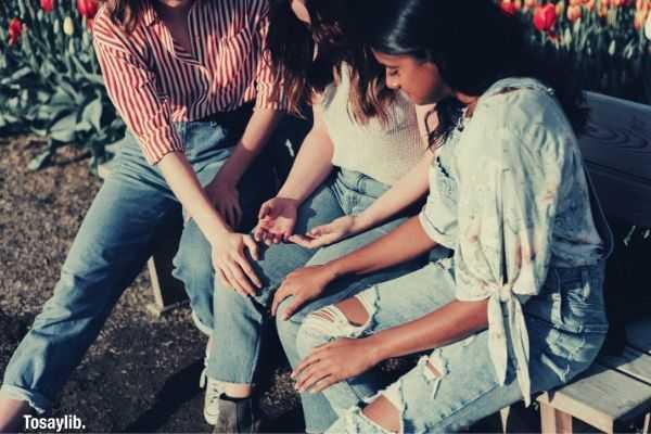 04 three women wearing blue denim jeans sitting on wooden bench praying
