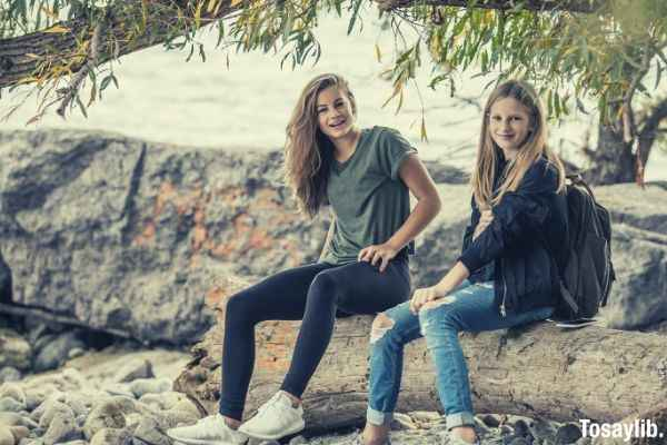 05 two long haired women sitting on rock under a tree during daytime wearing jeans