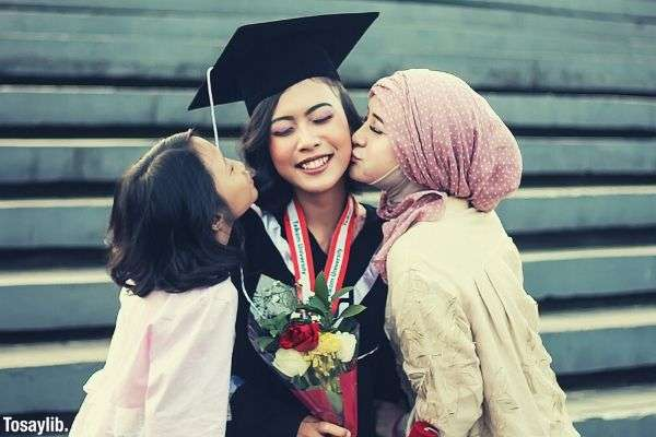two girls kissing woman in graduation gown holding flower
