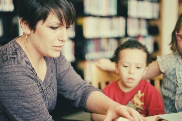 Preschool-teacher-in-gray-long-sleeve-shirt-sitting-beside-the-boy-in-orange-crew-neck-shirt