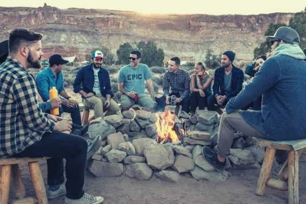 bonfire-surrounded-by-group-of-people-near-brown-hill-during-sunset-photo