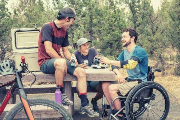 group-of-men-chilling-drinking-beverage-in-can-one-sitting-on-wheelchair