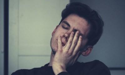 man-wearing-black-crew-neck-top-touching-his-eyes-depressed