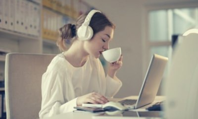 woman-in-white-dress-shirt-using-white-laptop-computer-and-drinking-on-her-white-cup