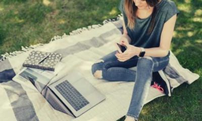 young-student-using-mobile-while-sitting-in-park-with-laptop-picnic-blanket