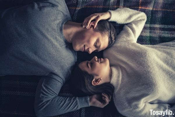 man and woman lying on the bed both wearing sweater long sleeves