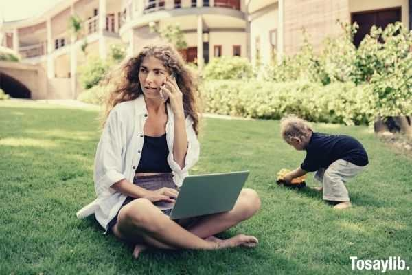 photo of woman using silver laptop with her child playing on grass field talking about something urgent over the phone