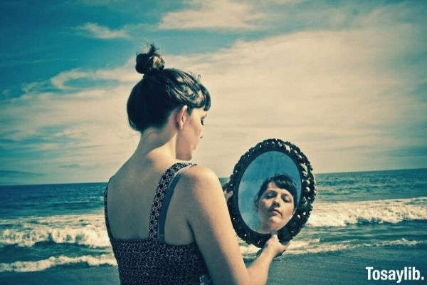 woman in sleeveless on the beach looking at the mirror