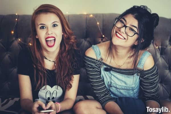 two cute women smiling one wearing black shirt and one on jumper sitting on the sofa