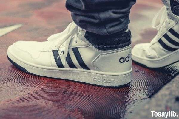 white and black adidas low top sneakers on wet floor