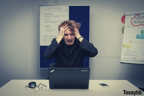 man wearing black holding his hair last minute meeting for work problem lenovo thinkpad laptop