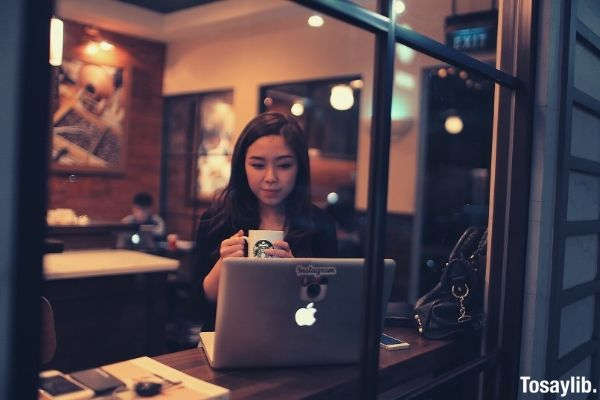 people coffee shop computer woman holding mug of coffee macbook