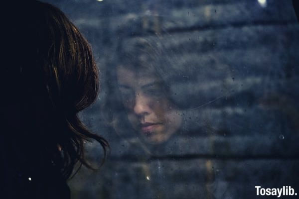 woman looking outside the window batlling depression
