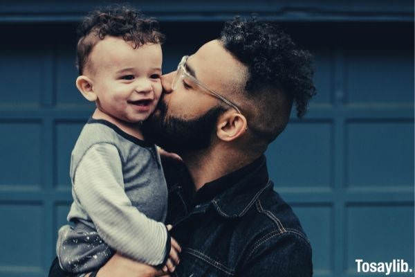 man in black denim polo with undercut hair carrying baby and kissing him