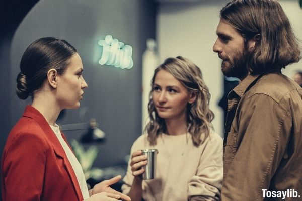 two woman and a man talking while woman in pink holding beverage