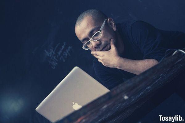 man using silver macbook bald wearing white eyeglasses