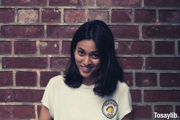 beautiful woman smiling wearing white shirt with taco me out logo printed brick wall