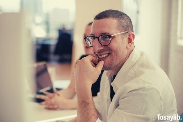 man in white polo wearing black and white eyeglasses smiling looking at something
