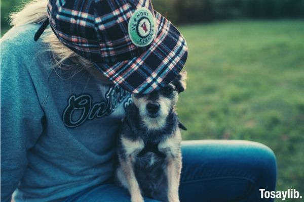 person with gray jacket and stripes black hat vermont flanel carrying a dog