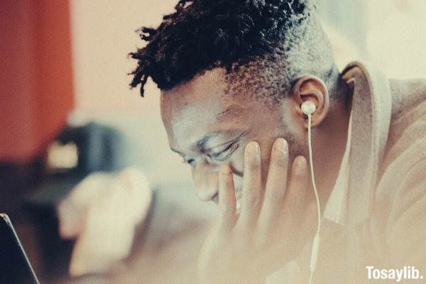 black man curly undercut hair smiling wearing earphones while looking at the laptop