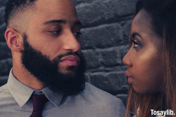 man in formal attire with maroon tie and beard looking at his woman saying some encouraging words to boyfriend
