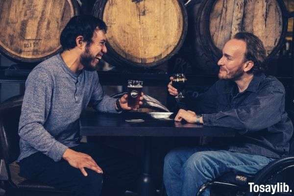 two men sitting beside barrels drinking beer while talking with each other