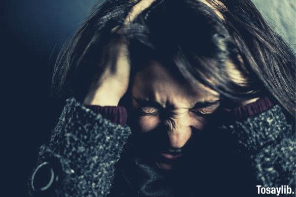 stressed young woman holding her head while in pain