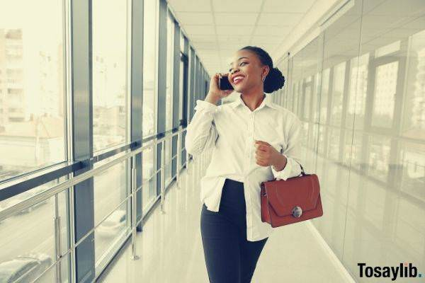 cheerful woman happy friday mood talking on smartphone in the office