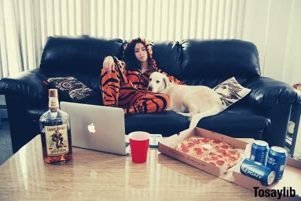 woman on the black sofa wearing tiger costume beside the white dog with laptop bear pizza in front