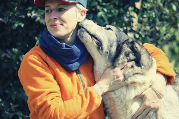 Lovely-dog-emotional-support-animal-smelling-its-owner-on-orange-and-blue-jacket-while-hugging