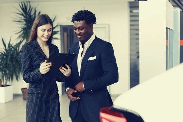black man and white woman in formal attire talking man hand resume to friend