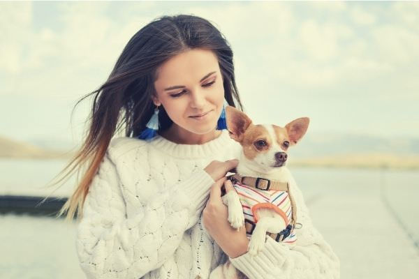 cute-woman-in-white-sweater-carrying-cute-dog-outside-sky-clouds