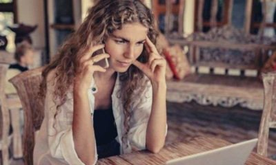 photo-of-blonde-curly-haired-woman-trying-to-find-excuses-to-get-off-the-phone-quickly-while-in-front-of-laptop