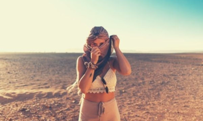 feature-words-to-describe-heat-woman-standing-in-the-middle-of-the-desert-covering-her-face