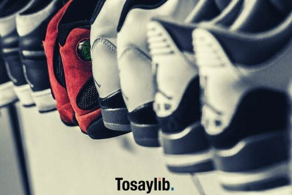 several white and black sneakers and a red sneaker in the middle