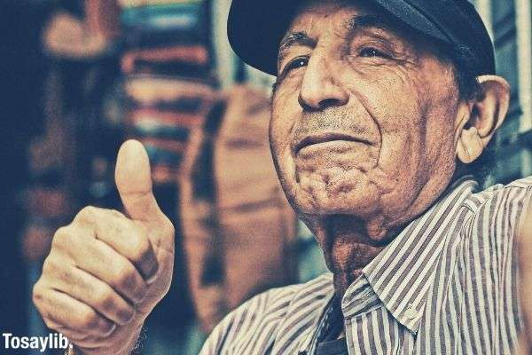old man in stripes and baseball cap making thumbs up sign