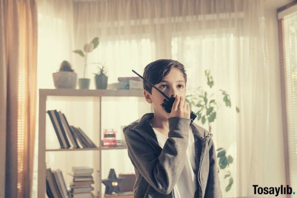 boy in gray hoodie using walkie talkie interphone divider on the back with books and plants curtain