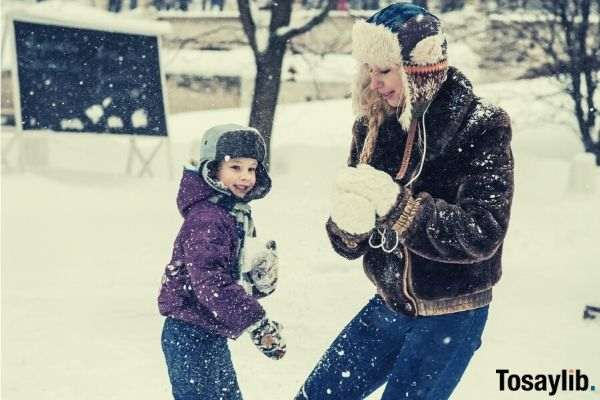 woman and child wearing snow attire playing with snow