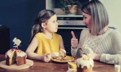 feature-how-to-say-yes-young-girl-in-yelow-mom-in-white-knitted-tops-thumbs-up-to-her-child-eating-cake