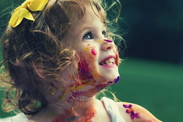 feature-words-to-describe-child-cute-girl-in-tank-top-paint-all-over-her-face-and-body