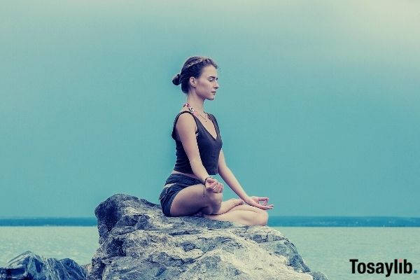 concentrated yoga teacher wearing tank top meditating on large stone skies sea