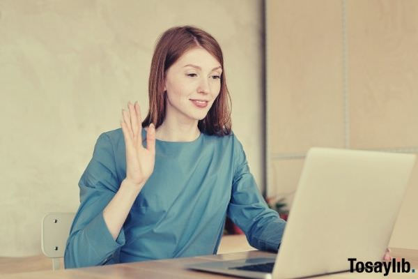 woman in blue long sleeve blouse sitting waving hello on laptop
