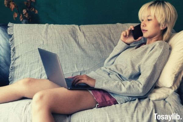 ethnic freelancer typing on laptop and speaking on smartphone wearing longsleeves and shorts sitting on the sofa