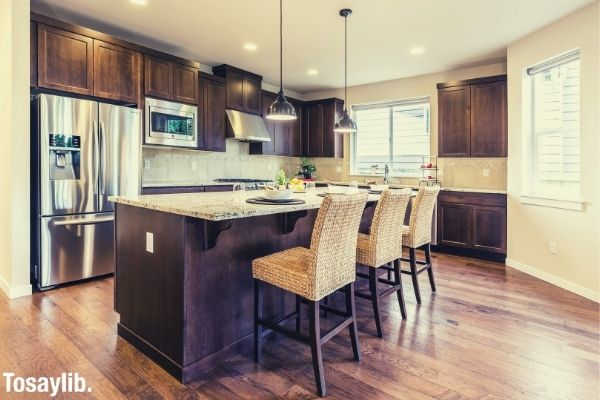 kitchen counter top clean architectural modern design chairs lights refrigerator