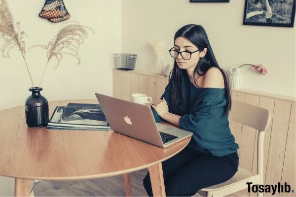thoughtful female freelancer watching laptop in light room at home while having coffee