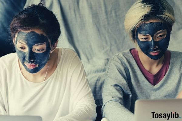two women wearing longsleeves black facial masks while using laptops at home