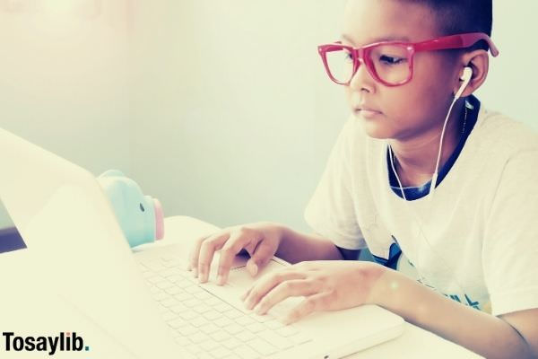 little boy listening and using laptop computer typing wearing white shirt and red glasses