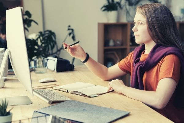 girl-holding-pencil-while-looking-at-imac-netiquette-rules-wearing-dark-orange-shirt-and-sweater-wrapped-around-her-shoulder