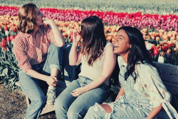 three-women-sititng-on-the-wooden-bench-by-the-tulip-flower-field-words-to-describe-youth
