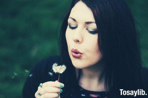 beautiful woman in black shirt blowing white dandelion flower